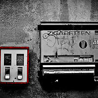 A cigarette machine hangs next to a gum machine on a farmhouse wall in Germany