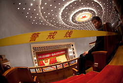 A Chinese security officer is seen guarding the audience seats behind a security barrier during the opening session of the National Peoples Congress (NPC) in the Great Hall of the People in Beijing, China, on 05 March 2011. The NPC has over 3,000 delegates and is the world's largest parliament or legislative assembly though its function is largely as a formal seal of approval for the policies fixed by the leaders of the Chinese Communist Party.