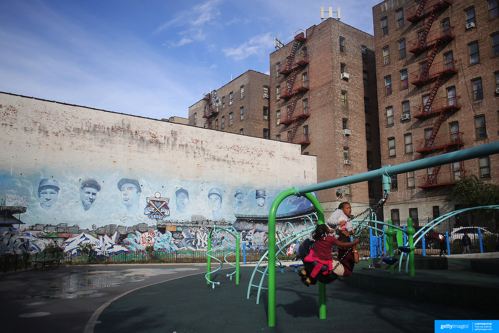 Yankee players murals on a playground wall as children play in the Bronx near Yankee Stadium before the New York Yankees V Baltimore Orioles American League Division Series play-off decider at Yankee Stadium, The Bronx, New York. 12th October 2012. Photo Tim Clayton