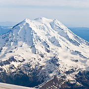 "In altitude, Washington varies from sea level up to 14,411 feet (4,392 meters) at the summit of Mount Rainier, which is the highest peak in the Cascade Range. With 26 major glaciers, Mount Rainier is the most heavily glaciated peak in the lower 48 states, with 35 square miles (91 km²) of permanent snowfields and glaciers. This active stratovolcano (composite volcano) is in Pierce County, 54 miles (87 km) southeast of Seattle. Global warming and climate change: Mount Rainier's glaciers shrank 22% by area and 25% by volume between 1913 and 1994 in conjunction with rising temperatures (Nylen 2004). As of 2009, monitored glaciers are continuing to retreat (NPS). Over the last century, most glaciers have been shrinking across western North America (Moore et al. 2009) and the globe (Lemke et al. 2007) in association with increasing temperatures. Published in ""Light Travel: Photography on the Go"" book by Tom Dempsey 2009, 2010."