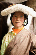 This girl wears a costume distinct of her tribe in a remote area of Tibet (Yushu (Jyekundo), China (Tibet)).