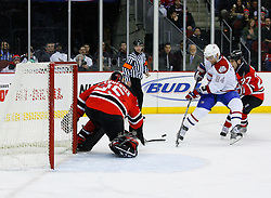 Jan 2, 2009; Newark, NJ, USA; New Jersey Devils goalie Scott Clemmensen (35) makes a poke check save on Montreal Canadiens left wing Guillaume Latendresse (84) during the first period at the Prudential Center.
