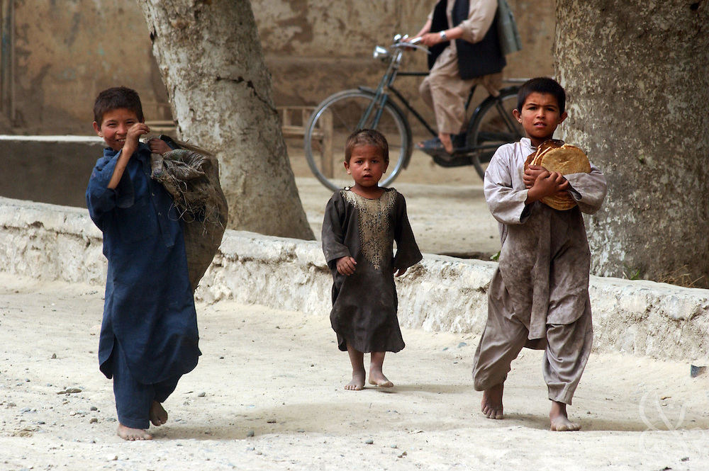 Poor Afghan children walk the streets June 8, 2002 in Kunduz, Afghanistan. Soldiers with the U.S. Army 489th Civil Affairs battalion are overseeing the reconstruction of local schools and funding civil humanitarian projects that will encourage growth in the local economy as part of the Operation Enduring Freedom military campaign in Afghanistan.
