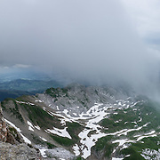 Rain clouds quickly descend. Säntis (2502 m / 8218 feet) is the highest peak of the Alpstein range and the Appenzell Alps, in Switzerland, Europe. Shared by three cantons, Säntis can be reached easily via aerial tramway (Luftseilbahn) from Schwägalp, or with effort via wonderful trails, to see vast mountain views across six countries: Switzerland, Germany, Austria, Liechtenstein, France and Italy. We highly recommend staying overnight on top as we did at Berggasthaus Alter Säntis, a fifth-generation family-run mountain inn since 1850, offering modern private double and dormitory lodging with good food and magnificent views. From where we joined it at Rotsteinpass, the spectacular, rocky Lisengrat trail to Säntis is rigged with safety cables in case of icy or wet conditions (and can be scary for those with fear of heights). In rainy weather the next day, we took the easy tram down instead of hiking to Ebenalp. The Appenzell Alps rise between Lake Walen and Lake Constance. This image was stitched from multiple overlapping photos.