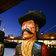 """SHOT 12/18/2007 - A wooden carved cowboy outside Native Traditions art, jewelry and crafts store in Old Town Scottsdale. Scottsdale, Az. is a city in Maricopa County, Arizona, United States, adjacent to Phoenix. Scottsdale has become internationally recognized as a premier and posh tourist destination, while maintaining its own identity and culture as """"The West's Most Western Town."""" What had, in the twentieth century been vacant desert, was converted to urban or suburban environment. The 2000 Census found the city's population to be 202,705, while according to the 2007 Census Bureau estimates, the population of the city was 240,410. Includes images of Old Town Scottsdale..(Photo by Marc Piscotty/ © 2007)"""