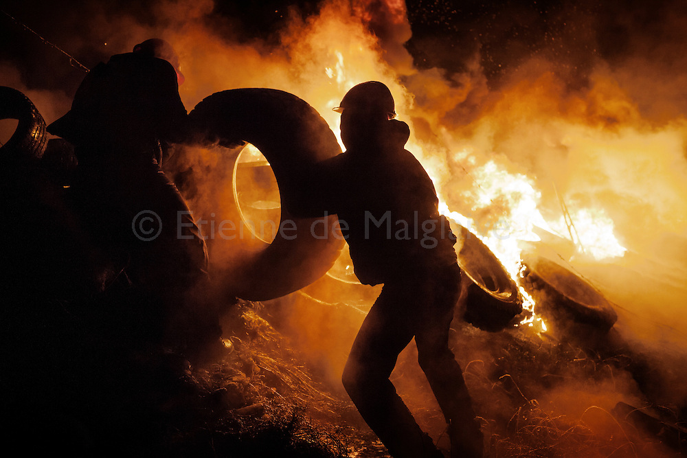 Protesters feed a fire barricade with tires during clashes  between antigovernment protesters and riot police on Hrushevskoho street, near Maidan Square, in Kiev. 24 January 2014