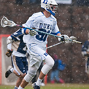Duke defender Luke Duprey #91 brings ball up field. The third-ranked Fighting Irish defeated sixth-ranked Duke, 13-5, in men's lacrosse action on a snowy Saturday afternoon at Koskinen Stadium in Durham, N.C.