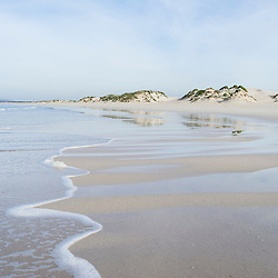 Pristine sandy beach and sand dunes on an incoming tide, De Mond Nature Reserve, Western Cape, South Africa
