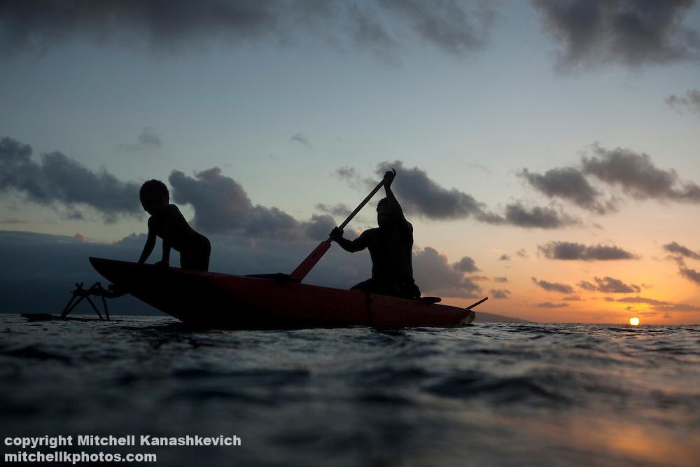 Father and son paddle through a lagoon at sunset. Rah Lava Island, Torba Province, Vanuatu