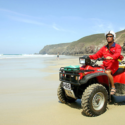 RNLI Lifeguard on patrol at Chapel Porth, St Agnes, Cornwall, UK