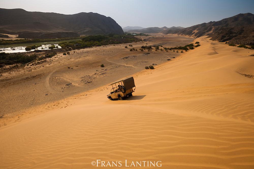Safari vehicle driving down sand dune towards Kunene river, Serra Cafema, Kaokoland, Namibia