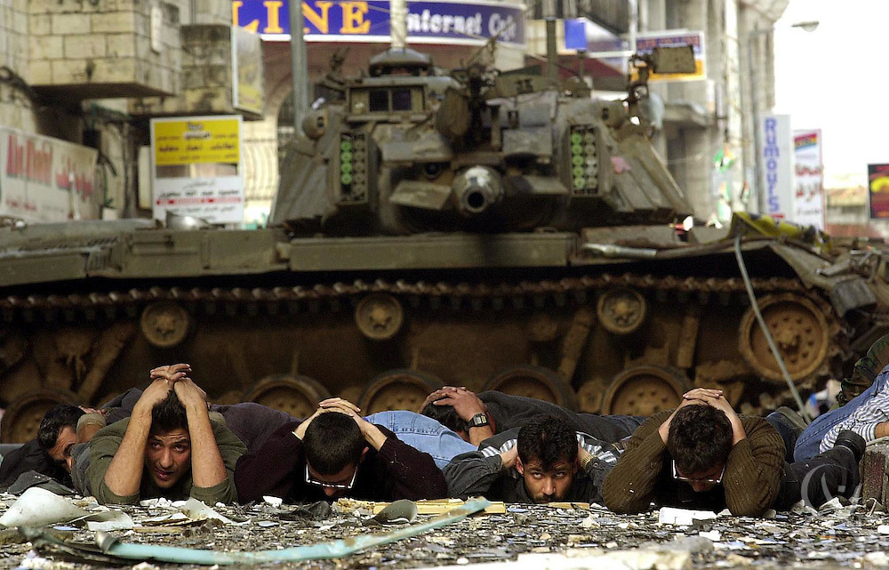 Palestinians surrender to Israeli soldiers during the March 30 2002 occupation of the West Bank town of Ramallah.  The Israeli army is in the process of a massive military operation which began yesterday with the seige and capture of Palestinian leader Yasser Arafat's Ramallah headquarters.