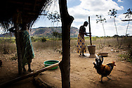 Hilda Daniel pounding maze at her home. Hilda, a 25 years old mother of four, lost her one and half year old son Edmilson from diarrhoea in March 2014. Namaveresse, Maua District, Mozambique