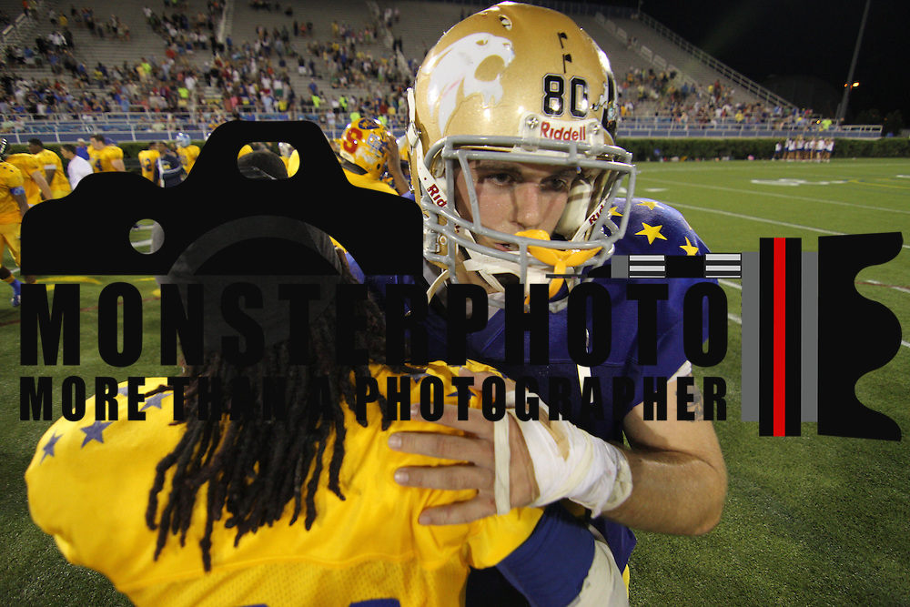 Gold Donovan Cain (21) of Dover High School hugs Blue James Rendle (80) of Saint Elizabeth High School after the playing of the 58th Annual DFRC Blue-Gold All?Star Football game Saturday, June. 22, 2013, at Delaware Stadium in Newark DE. &nbsp;&nbsp;<br /> <br /> Gold escape the blue squad 22-19