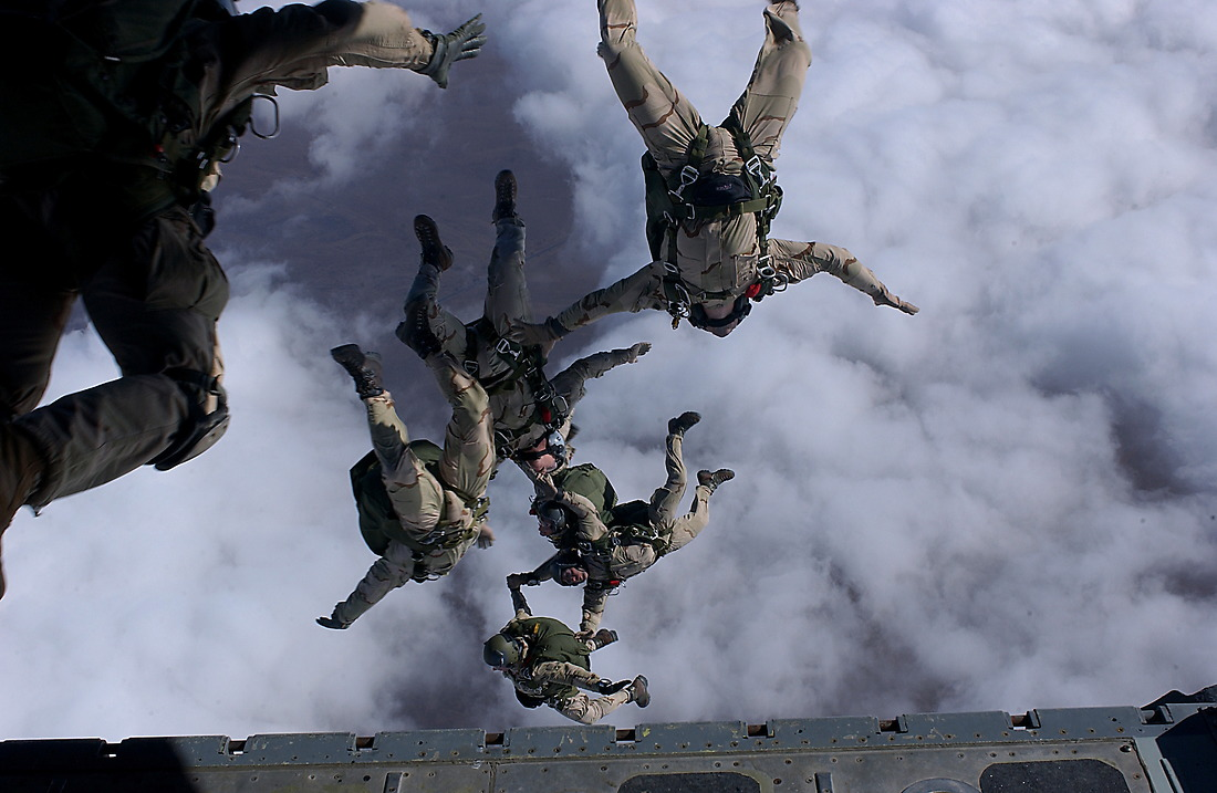 """""""That others may live"""", pararescue men from the 38th Rescue Squadron, Moody AFB, Georgia, and the 58th Rescue Squadron, Nellis AFB, Nevada, jump from a C-130 for a High Altitude Low Opening (HALO) free fall drop from 12999 feet on Friday, February 28, 2003, at an undisclosed location in support of Operation Enduring Freedom. Pararescue's mission is the recovery of downed aircrew members and or isolated personnel. Using a C-130 to jump in provides pararecue the fastest way to get to the distressed and provide them with medical attention, protection, and survival. — © SSgt. Jeremy T. Lock/"""