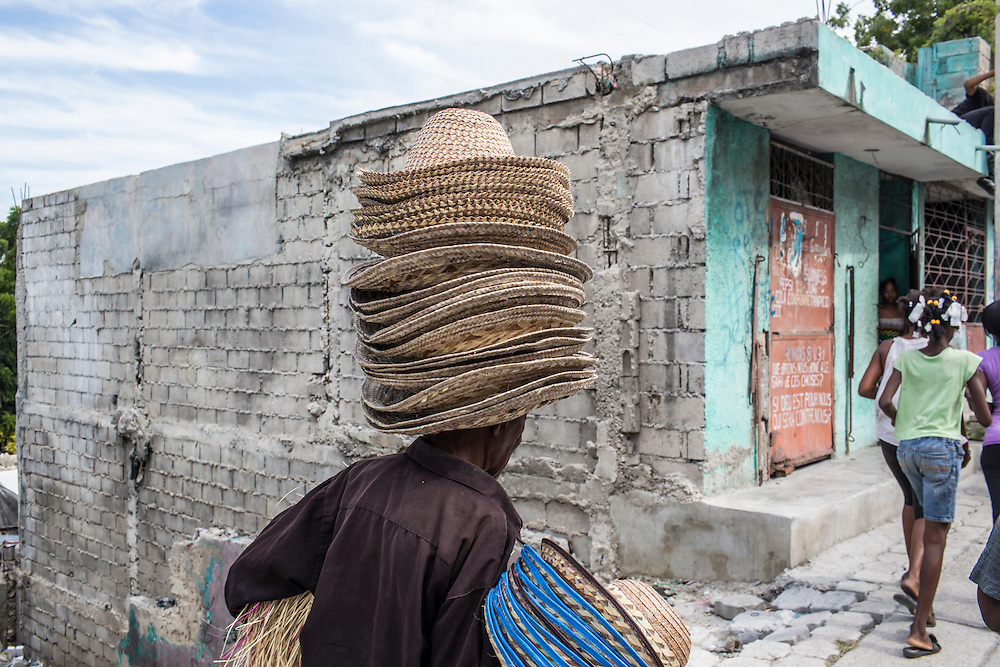 A man sells hats to block the strong sun during an anti-government protest on Tuesday, December 16, 2014 in Port-au-Prince, Haiti. President Michel Martelly was elected in 2010 with great hope for reforms, but in the wake of slow recovery and parliamentary elections that are three years overdue, his popularity has suffered tremendously, forcing Prime Minister Laurent Lamothe to resign.