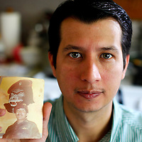 Oscar Ramirez Castaneda holds an undated photo of Lieutenant Oscar Ovidio Ramirez Ramos while posing for a photo in the kitchen of his home  in Framingham, Massachusetts on May 13, 2012.  Oscar was adopted by the Lieutenant at the age of 3 after the Lieutenant and his fellow Kaibil troops led a massacre in young Oscar's village in Guatemala.  Matthew Healey for ProPublica