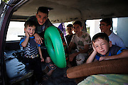 A bunch of kids in a van awaiting an excursion on a holiday to a big fresh water spring far outside of Koreen to enjoy the hot summer day bathing in the lake.<br />