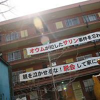 """AUM SHINRIKYO CULT HEADQUARTERS. Two banners, placed by local residents, with slogans against 'Aum Shinrikyo' Supreme Truth Cult, now known as 'Aleph', hang on the upper levels of a building. The floors below the banners are the cult's headquarters. Top banner reads """"We won't forget Aum carried out the sarin gas attacks"""", bottom banner reads """"Don't make the parents cry, give up and get out."""" Tokyo."""