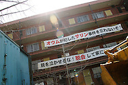 "AUM SHINRIKYO CULT HEADQUARTERS. Two banners, placed by local residents, with slogans against 'Aum Shinrikyo' Supreme Truth Cult, now known as 'Aleph', hang on the upper levels of a building. The floors below the banners are the cult's headquarters. Top banner reads ""We won't forget Aum carried out the sarin gas attacks"", bottom banner reads ""Don't make the parents cry, give up and get out."" Tokyo."