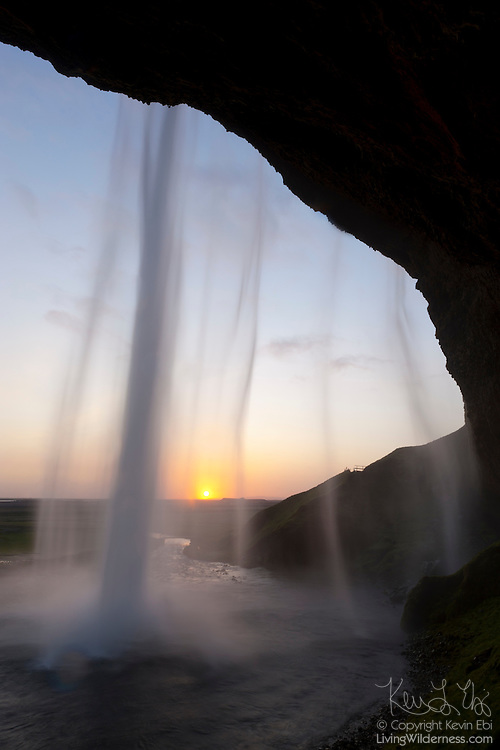 The setting sun shines through the Seljalandsfoss, a 200-foot (60-meter) waterfall in southern Iceland.