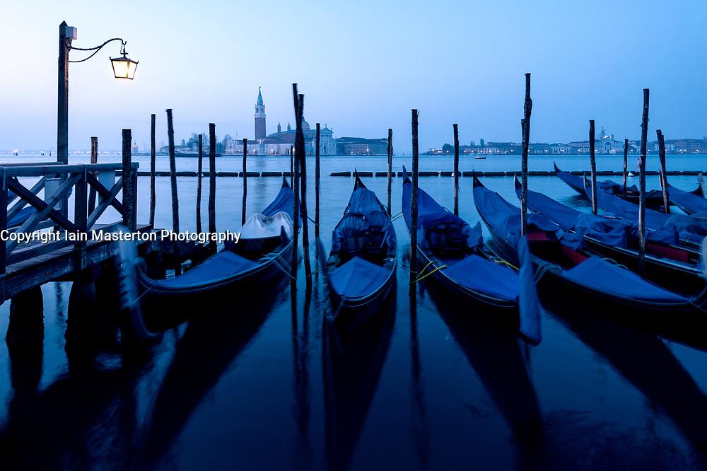 Dawn view of gondolas moored in Venice , Italy