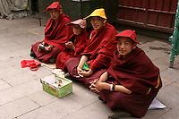 Tibetan Novice Monks taking a break from their kora circumnavigation at Barkhor Square.