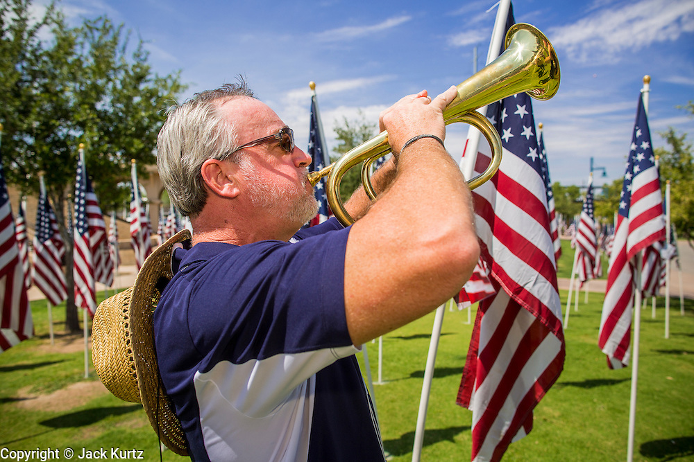 10 SEPTEMBER 2012 - TEMPE, AZ:  MARK POISSON, President of the Exchange Club of Tempe, plays Taps at the Healing Field in Tempe, AZ, Monday. The Exchange Club of Tempe and the city of Tempe are hosting the 9th Annual Healing Field display. The annual event posts three thousand American flags in the Tempe Beach Park. The flags are 3?X5?  and stand 8? tall. The display is a tribute to those who died in the terrorist attacks of September 11, 2001. Nearly 3,000 people were killed when terrorists affiliated Al-Qaeda crashed commercial airliners into the World Trade Center in New York, the Pentagon in Arlington, VA, and a field in Ohio.   PHOTO BY JACK KURTZ
