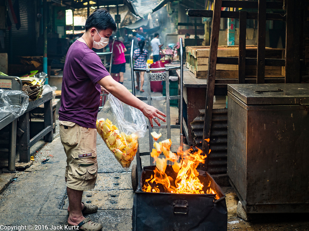 """07 FEBRUARY 2016 - BANGKOK, THAILAND: A man burns """"ghost money"""" to make merit for Chinese New Year in Bangkok's Chinatown. Chinese New Year, also called Lunar New Year or Tet (in Vietnamese communities) starts Monday February 8. The coming year will be the """"Year of the Monkey."""" Thailand has the largest overseas Chinese population in the world; about 14 percent of Thais are of Chinese ancestry and some Chinese holidays, especially Chinese New Year, are widely celebrated in Thailand.        PHOTO BY JACK KURTZ"""