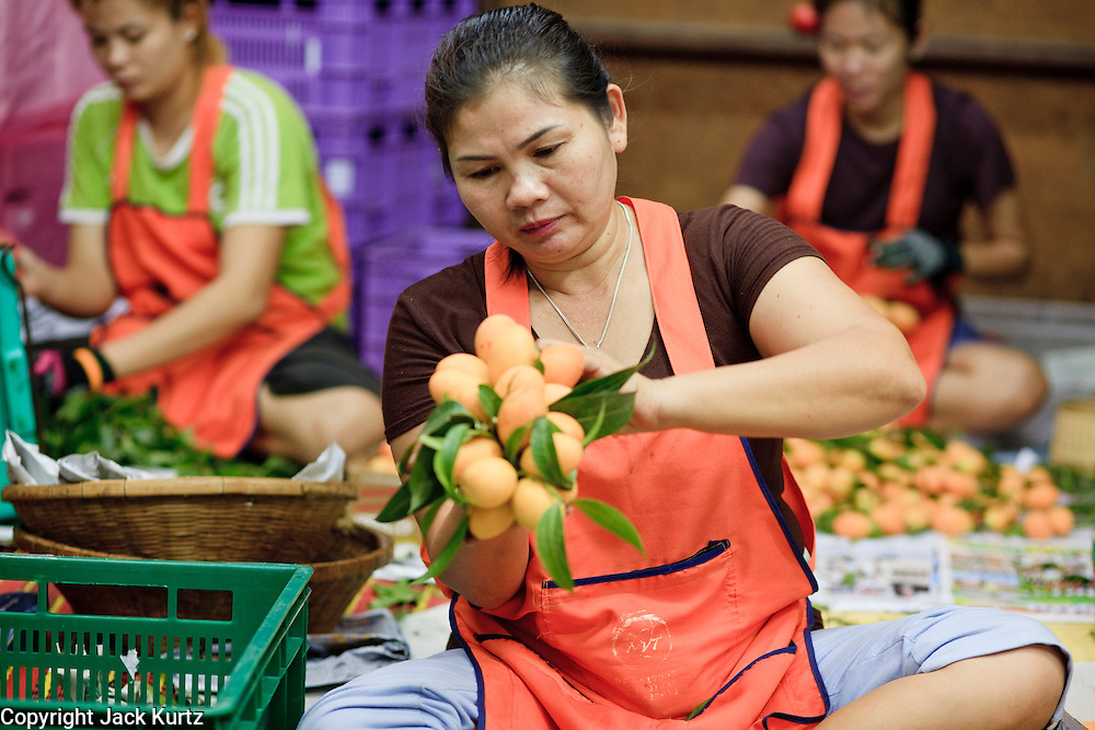 """Mar. 9, 2009 -- BANGKOK, THAILAND: Women package and sort fruit in the flower and produce market on the Chao Phraya River in Bangkok. Every morning, flowers and produce from the provinces arrive in the market where they are bundled and sold at retail in Bangkok's consumer markets. Many of the flowers are sold in and around the Buddhist temples in Bangkok. People buy them as offerings or to """"make merit."""" Photo by Jack Kurtz / ZUMA Press"""