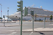Docked at a quay and overlooked by a landscape of street lighting and posts, the cruise liner Costa Magica awaits its passengers after their excursion to the Portuguese capital, on 12th July, 2016, in Lisbon, Portugal. The ship is enormous, at 105,000 tons and carrying 2,720 passengers. <br /> Debuting in 2004 as a sister ship to Costa Fortuna, it is built on the same platform as the Destiny-class of the Carnival Cruise Lines. (Photo by Richard Baker / In Pictures via Getty Images)