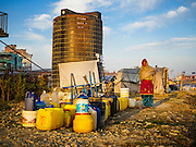 04 MARCH 2017 - KATHMANDU, NEPAL: A woman waits for water at an empty water tank in an IDP camp in the center of Kathmandu. She later learned the water tank is no longer being filled. The camp opened days after the April 2015 earthquake devastated Nepal, killing almost 9,000 people. At its peak, about 1,800 families lived in the camp. The camp is still open nearly two years after the earthquake, about 400 families currently live in the camp. Camp residents say the Kathmandu municipal government is trying to close the camp and is encouraging residents to find new housing. They said the government is cutting off services to the camp and last week stopped the free distribution of water, although water can be purchased for delivery. Most of the people in the camp came to Kathmandu from rural villages in the mountains in the weeks after the earthquake. Many of the residents of the camp, technically homeless, have found work in Kathmandu's bustling construction industry, rebuilding homes destroyed in the earthquake.       PHOTO BY JACK KURTZ