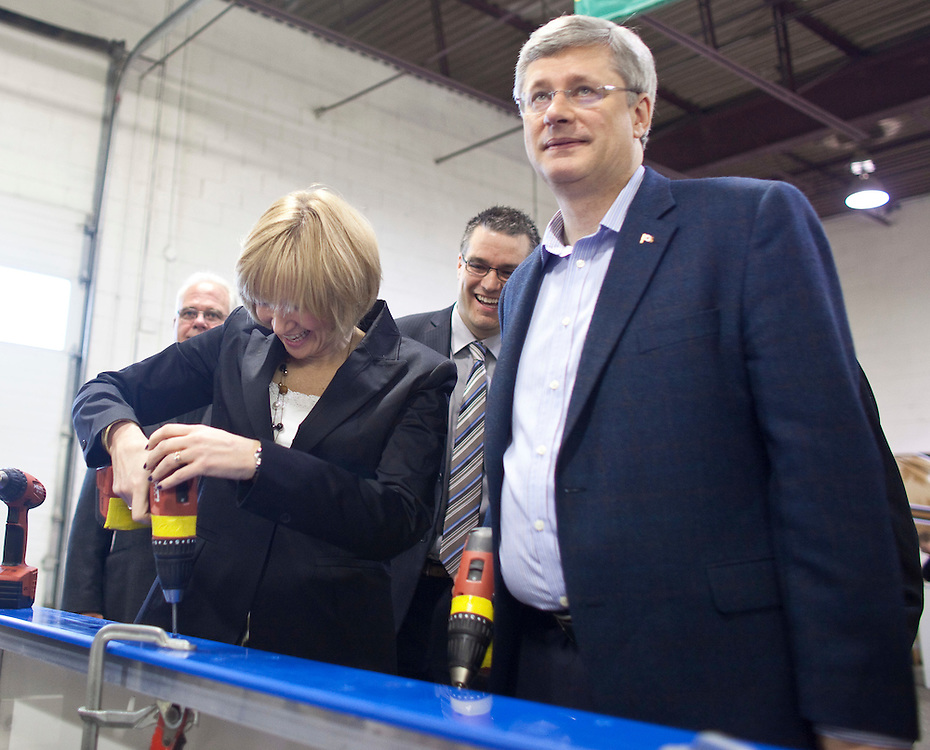 Conservative leader Stephen Harper looks away after his wife Laureen told the media that Harper once bought her a drill as a gift during a campaign stop at hockey boards marker Sport Systems Unlimited in Waterloo, Ontario, April 27, 2011. <br /> AFP/GEOFF ROBINS/STR
