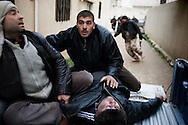 SYRIA - Homs province: Syrian men take a heavy wounded in a house used as hospital in Homs province on February 22, 2012. ALESSIO ROMENZI