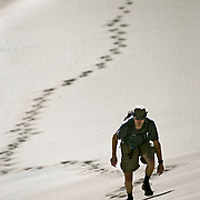 """Jim Hansman, 37, of Denver, Co. leaves tracks as he treks up a sand dune at Great Sand Dunes National Park and Preserve. Hansman said it was the first time he's been to Great Sand Dunes and said, """"it's beautiful and awesome"""". The park, located near Alamosa, is the state's newest national park and features stunning sand dunes that rise more than 700 feet above the floor of the San Luis Valley. Last year the National Park Service completed the conversion of Great Sand Dunes from a national monument to a national park. The park now encompasses some 150,000 acres and the dunes were formed by blowing winds that have carried sand across the San Luis Valley and deposited them at the base of the Sangre de Cristo Mountains for thousands of years. Great Sand Dunes National Park and Preserve is a United States National Park located in Alamosa County and Saguache County, Colorado, United States. Originally designated Great Sand Dunes National Monument, Great Sand Dunes National Park and Preserve was created by an act of the United States Congress on September 13, 2004. The park contains approximately 85,000 acres. The dunes were formed from sand deposits of the Rio Grande and its tributaries, flowing through the San Luis Valley. Over the ages, westerly winds picked up sand particles from the river flood plain. As the wind lost power before crossing the Sangre de Cristo Range, the sand was deposited on the east edge of the valley. This process continues, and the dunes are slowly growing. The wind changes the shape of the dunes daily. Digging a few inches into the dunes even at their peaks reveals wet sand. If the streams were to dry up, the dunes would disappear; in fact part of the motivation of turning the Monument into a National Park was the extra protection of the water, which Colorado's cities and agriculture covet..(MARC PISCOTTY/ © 2005)"""