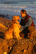 Golden Retriever and a man on cliff  by the ocean in Montauk, NY