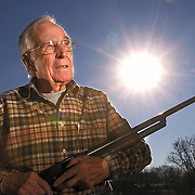 Photo by Gary Cosby Jr.  Gilbert Crutchfield holds a 12 gauge shotgun at his home in Tanner.  Sixty five years ago, Crutchfield was holding a shotgun on Pearl Harbor on that fateful morning when he encountered the Empire of the Rising Sun.