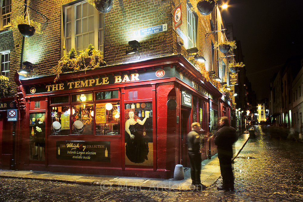 People standing outside an Irish pub called the Temple Bar at night, Dublin, Ireland.