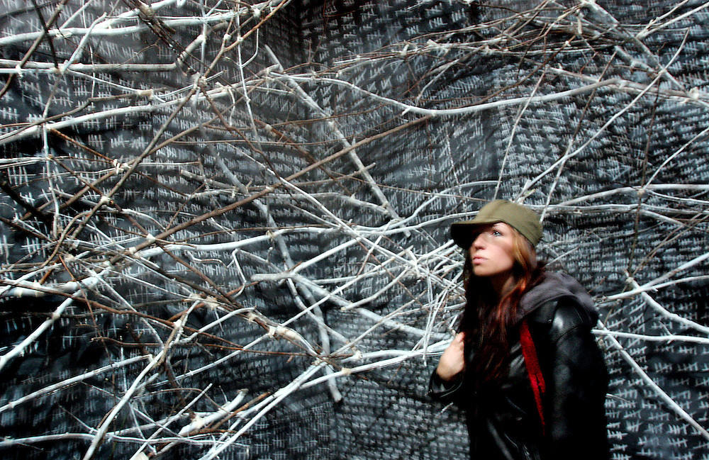 """12/01/05 Boston, MA-- Carissa Jope, 21, of Wenham, looks around inside a room designed like a nest, part of the """"Medicine Wheel"""" installation at the Cyclorama in honor of World AIDS Day Thursday.  (120105aidsar01, saved in fri, Staff Photo by Angela Rowlings)"""