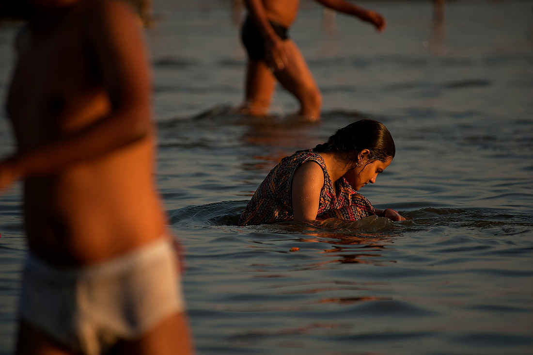 """A woman bathe's alone not bothered by the crowds on February 6, 2013 in Allahabad, India during the Kumbh Mela. """"Kumbh Mela"""" is a mass Hindu pilgrimage of faith in which Hindus gather to bathe in a sacred river. — © Jeremy Lock/"""