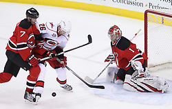 Feb 16; Newark, NJ, USA; New Jersey Devils defenseman Henrik Tallinder (7) ties up Carolina Hurricanes right wing Erik Cole (26) in front of New Jersey Devils goalie Johan Hedberg (1) during the third period at the Prudential Center. The Devils defeated the Hurricanes 3-2.