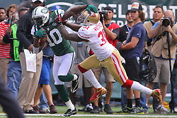 Sept 30, 2012; East Rutherford, NJ, USA; New York Jets wide receiver Santonio Holmes (10) catches a pass while being defended by San Francisco 49ers strong safety Donte Whitner (31) during the first half at MetLIfe Stadium.