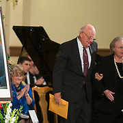 Judge Justin Quackenbush escorts Mrs. Heather Foley, wife of House Speaker Thomas Foley, from the stage during the memorial for the legendary leader Nov. 1, 2013 at St. Aloysius Church. (Photo courtesy of Gonzaga University)