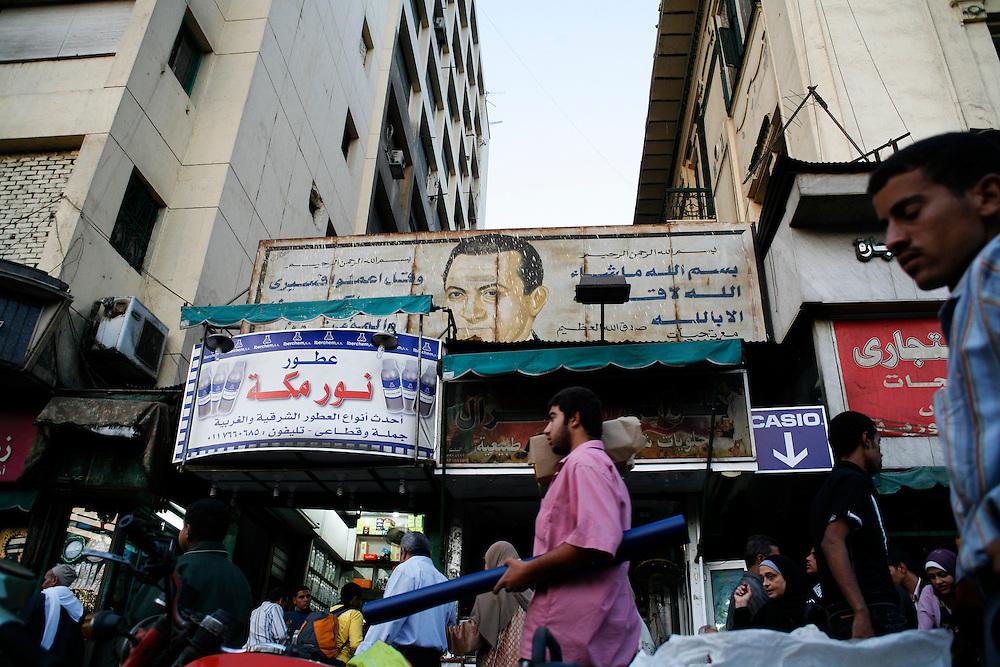 Street vendors in Cairo walk in front of a sign of Egyptian President Hosni Mubarak.
