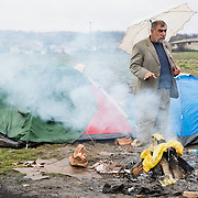 A man holding an umbrella tries to dry by an open fire at the transit camp of Idomeni, Greece. <br /> <br /> Thousands of refugees are stranded in Idomeni unable to cross the border. The facilities are stretched to the limit and the conditions are appalling.
