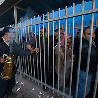 A Palestinian man sells coffee to Palestinian workers, as they  queue along the separation wall at the checkpoint 300, the crossing passage between Bethleem and Jerusalem, on December 15. 2010 in Bethleem.Workers arrived every day at two o'clock in the morning  to catch a place at the entrance of the checkpoint, so they can arrived at time to their work in the Israeli side. Photo by Olivier Fitoussi