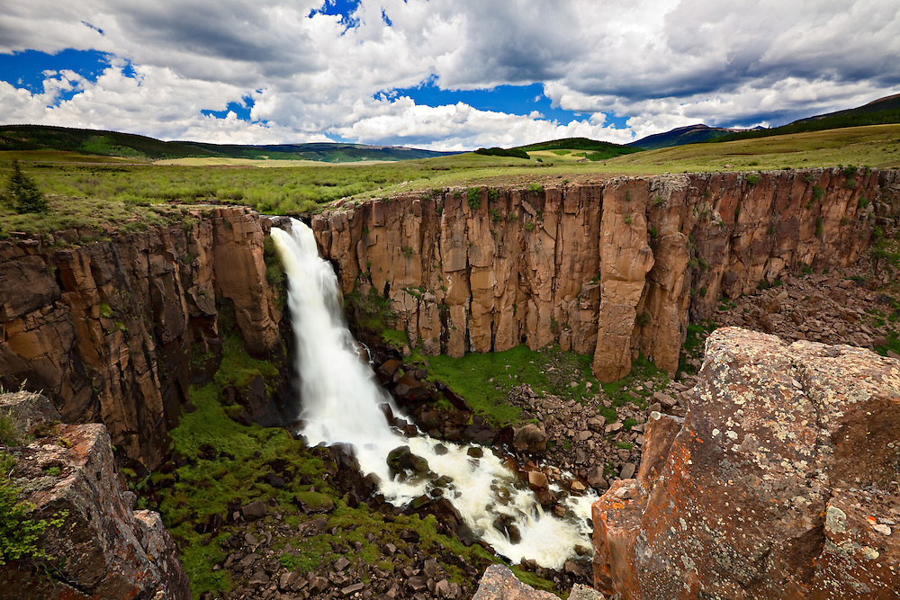 Spring runoff from the snow-melt cascades over a cliff. North Clear Creek Falls near Creede, Colorado.