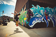 A skater jumps in Bushwick beside a wall covered with graffitis.