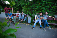 At right, Nasser and Muhannad, asylum seekers from Syria, sit with fellow migrants and refugees outside the asylum center serving as their temporary home on June 6, 2015 in Freyung, Germany. After passing through Eastern Europe, Muhannad and Nasser were caught by police on the German border where they were taken to an asylum center for processing. Ann Hermes/© The Christian Science Monitor 2015