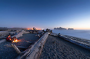 A couple enjoys a romantic candlelit twilight under the stars on Rialto Beach, Olympic National Park, on an unusually warm October 3rd. Giant driftwood logs—entire trees—litter the beach, washed up by surf that can reach 20-plus feet in winter. The lights in the background are at the harbor at La Push, across the river.